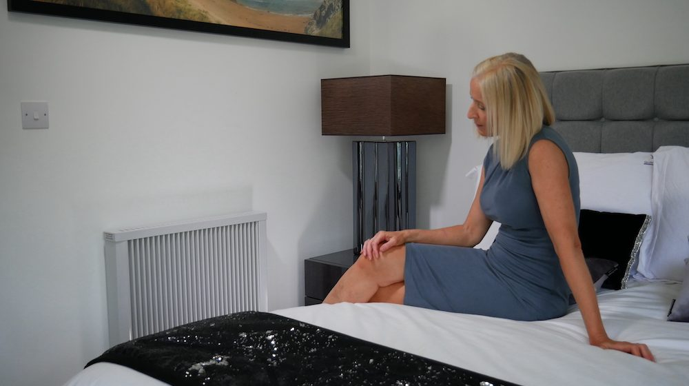 Woman sitting on bed next to radiator