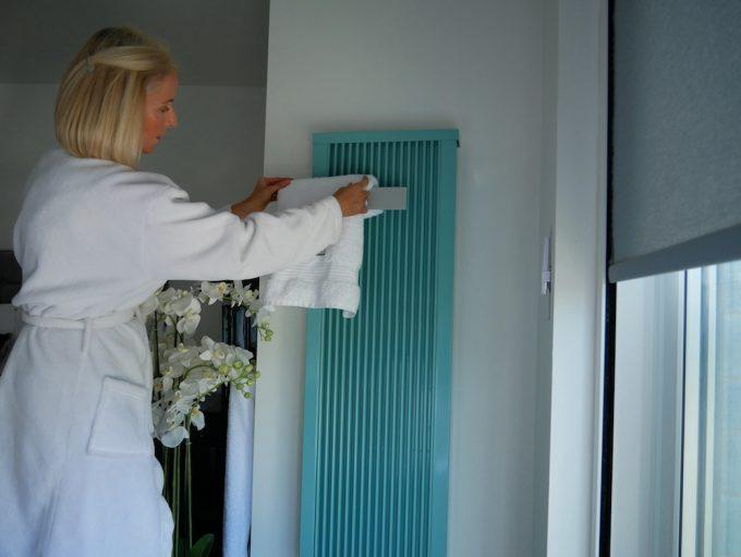 Woman adjusting towel on radiator